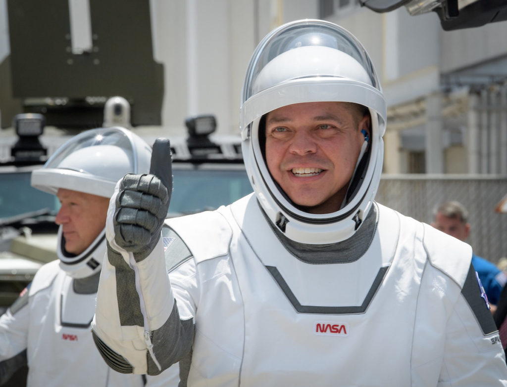 NASA astronauts Robert Behnken, foreground, and Douglas Hurley, wearing SpaceX spacesuits, are seen as they depart the Neil A. Armstrong Operations and Checkout Building for Launch Complex 39A to board the SpaceX Crew Dragon spacecraft for the Demo-2 mission launch. Image credit: NASA/Bill Ingalls