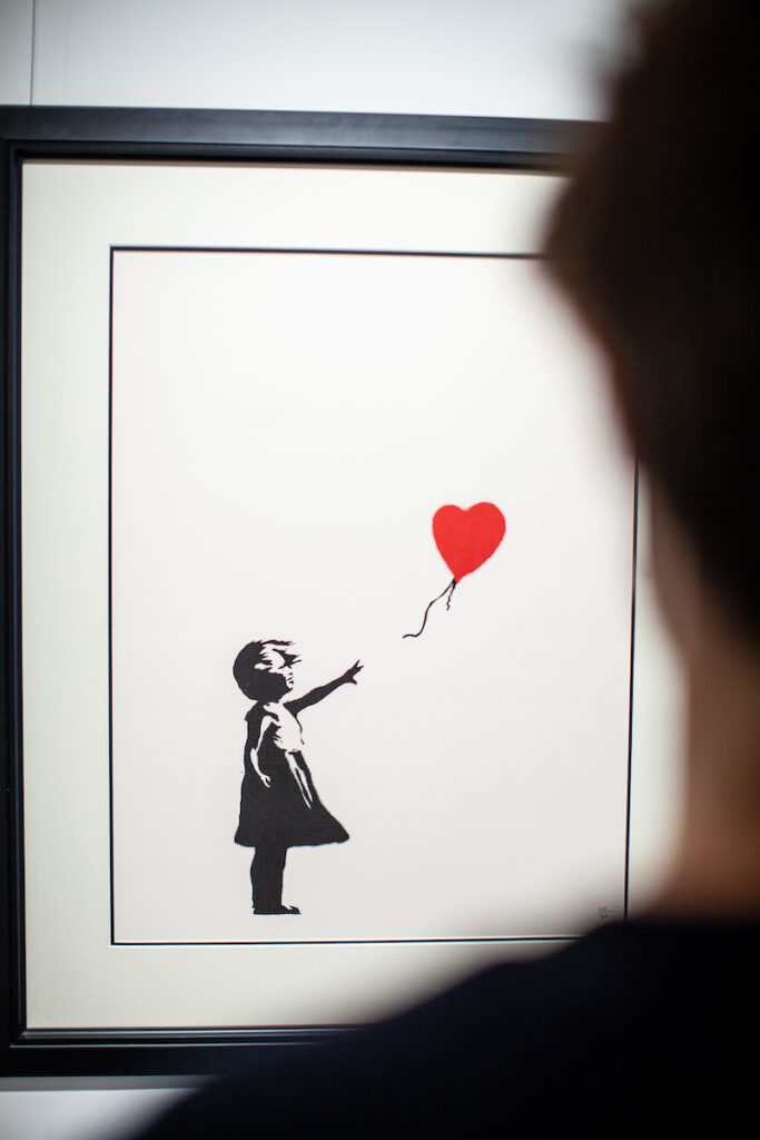 """If there is one thing you should know about NFT art, it's this: """"This isn't a fad. This is gonna go on for a lot longer.""""   Art investor views 'Girl with a Balloon', distinctive screen print by Banksy. Image credit: HOFA Gallery"""