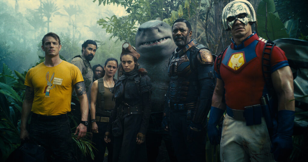 L-R: Joel Kinnaman as Colonel Rick Flag, Alice Braga as Sol Soria, Daniela Melchior as Ratcatcher 2, King Shark (voiced by Sylvester Stallone), Idris Elba as Bloodsport, and John Cena as Peacemaker. Image credit: Warner Bros. Pictures & DC Comics